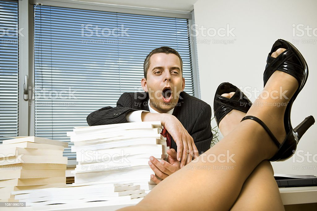 Businessman Staring at Woman's Legs stock photo