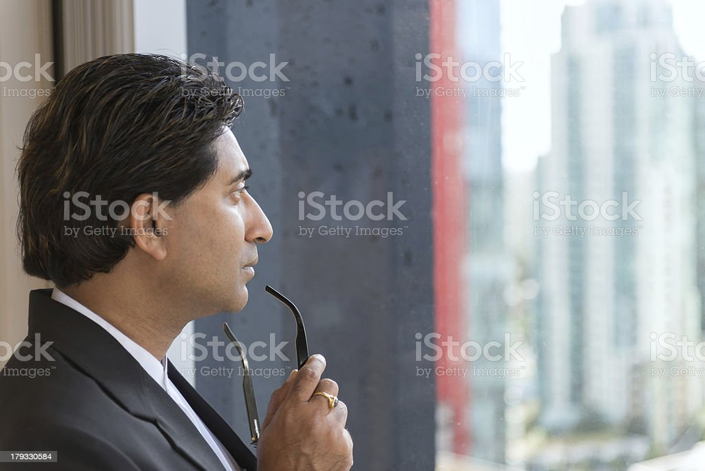 Businessman Staring out of Highrise Office Window royalty-free stock photo