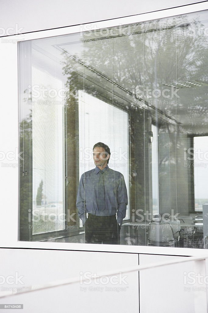 Businessman staring out office window royalty-free stock photo