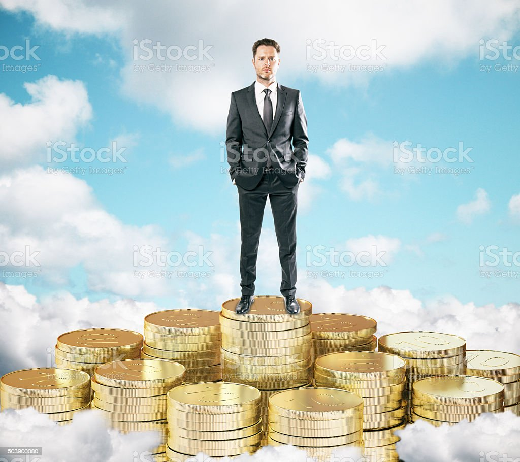 Businessman staying on pile of gold coins stock photo