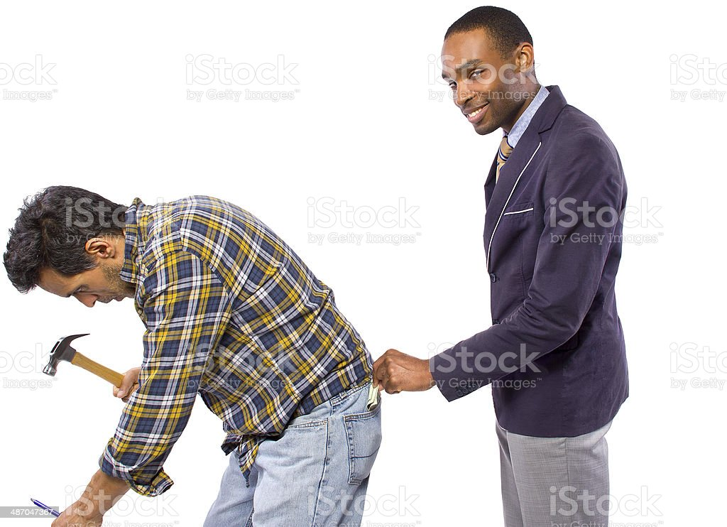 Businessman Stealing from the Poor Blue Collar Worker stock photo