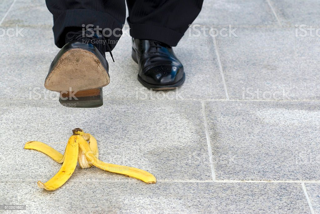 Businessman stepping on banana skin, copy space Businessman stepping on banana skin, copy space Adult Stock Photo