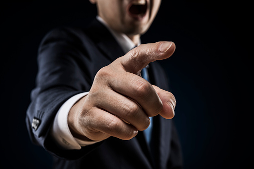 Businessman sticks out a finger and reproves it.
