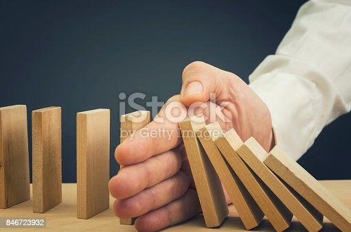 istock Businessman Stop Domino Effect 846723932