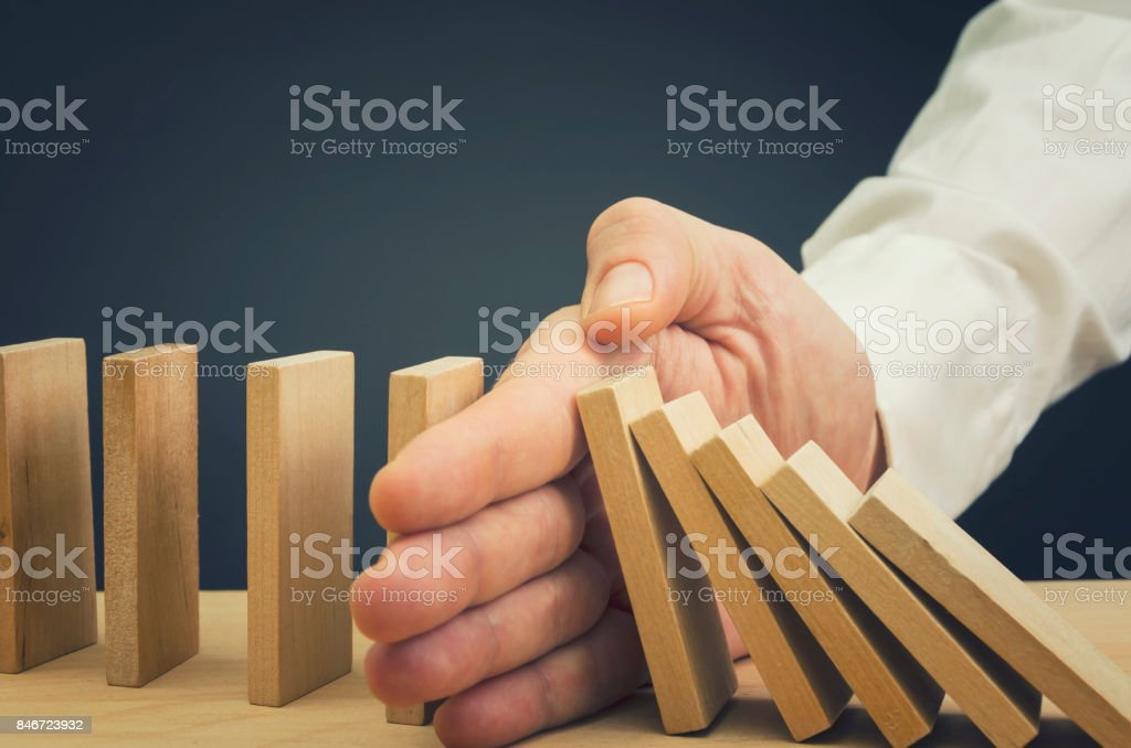 Businessman Stop Domino Effect stock photo