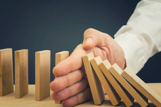 businessman stop domino effect - stability stock photos and pictures