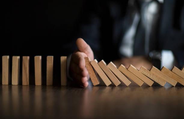 geschäftsmann stop domino effect. risikomanagement und versicherungskonzept - leitende position stock-fotos und bilder
