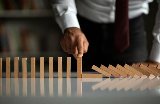 geschäftsmann stop domino-effekt. risikomanagement- und versicherungskonzept - abenteuer stock-fotos und bilder