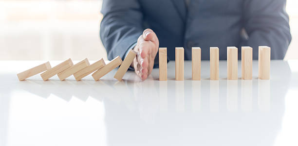 businessman stop domino effect. risk management and insurance concept - protection stock photos and pictures