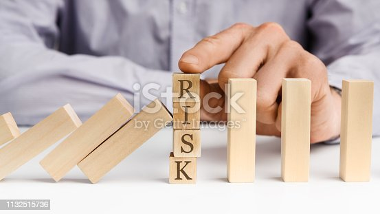 istock Businessman stop domino effect with word Risk 1132515736