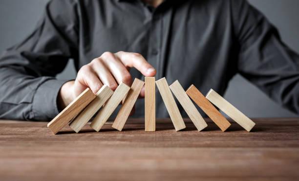 geschäftsmann, domino-effekt mit seinem finger zu stoppen. sicherheit und versicherung konzept. - interessiert stock-fotos und bilder