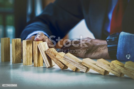 istock businessman stopping the domino effect 622993868
