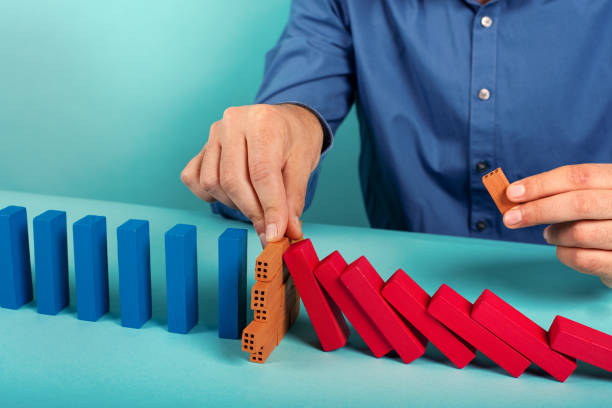 Businessman stops a chain fall like domino game. Concept of preventing crisis and failure in business stock photo