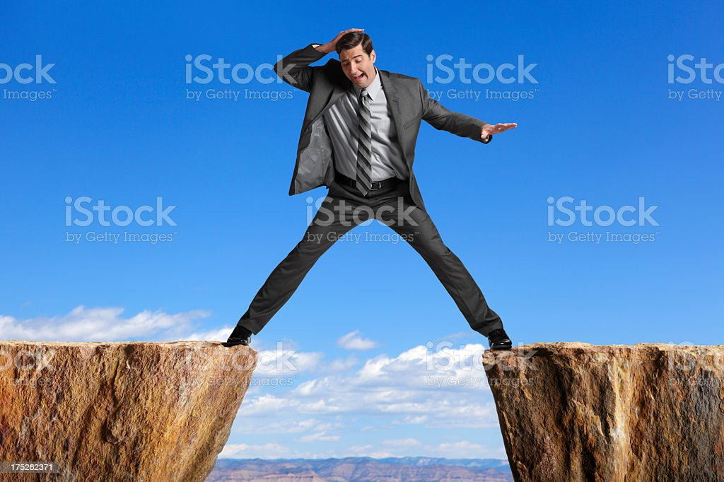 Businessman straddling the divide created by two cliffs stock photo