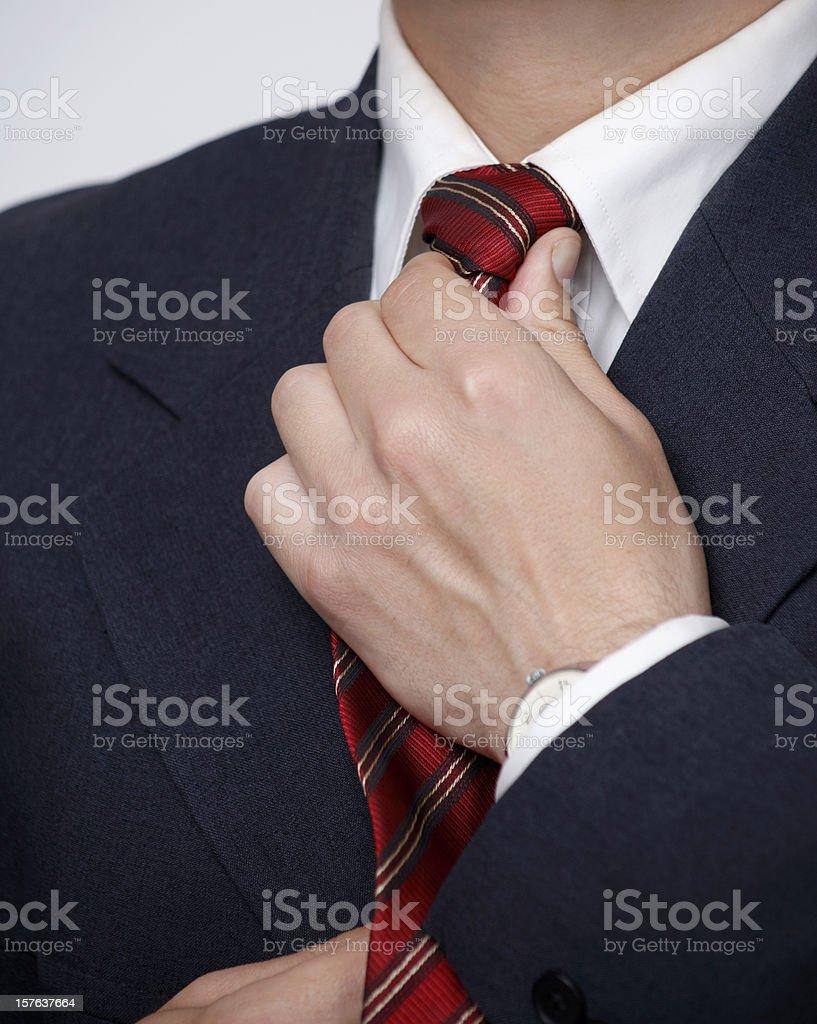 Businessman straightening his necktie knot royalty-free stock photo