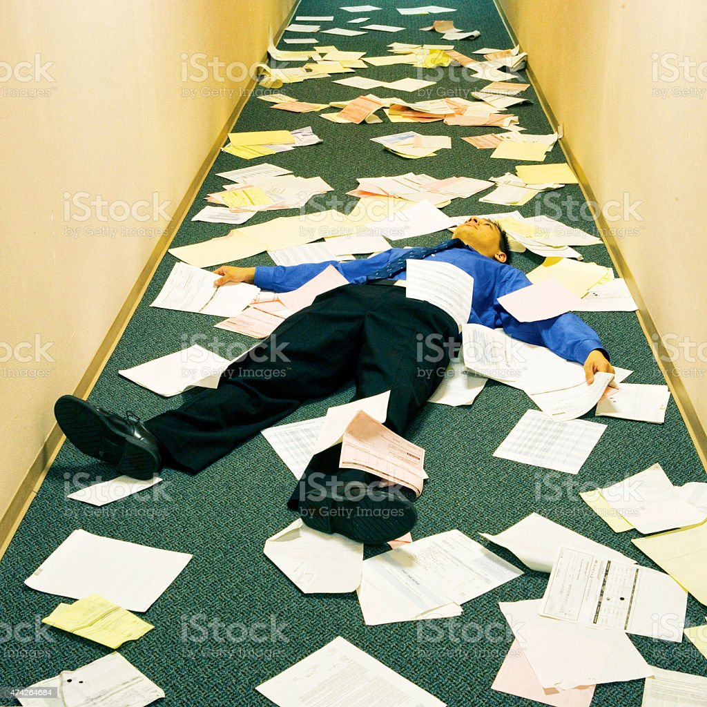 Businessman stressed laying down on floor with documents. stock photo