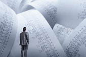 A man looks up at large rolls of calculator tape that have various amounts of purchases printed on it that represent his debt.