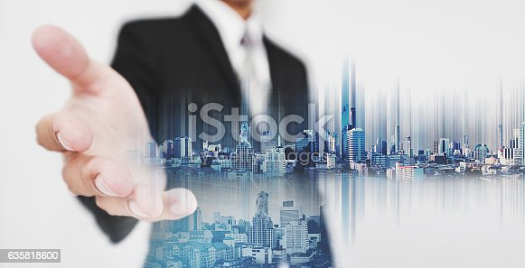 635942136istockphoto Businessman stretch out hand, with double exposure futuristic city 635818600