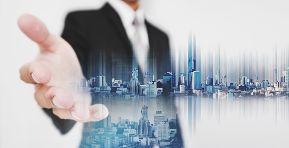635942136 istock photo Businessman stretch out hand, with double exposure futuristic city 635818600
