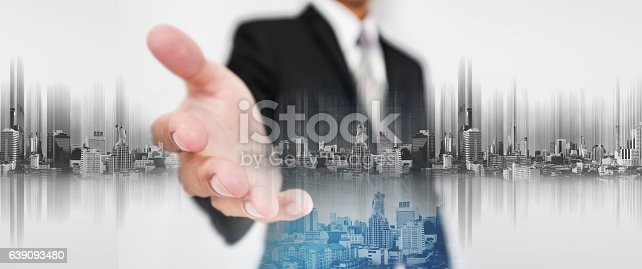 635942136istockphoto Businessman stretch out hand, with double exposure futuristic city 639093480
