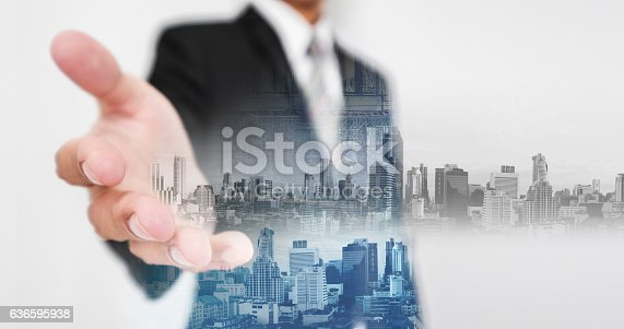 635942136istockphoto Businessman stretching hand, with double-exposure city and real-estate site construction 636595938