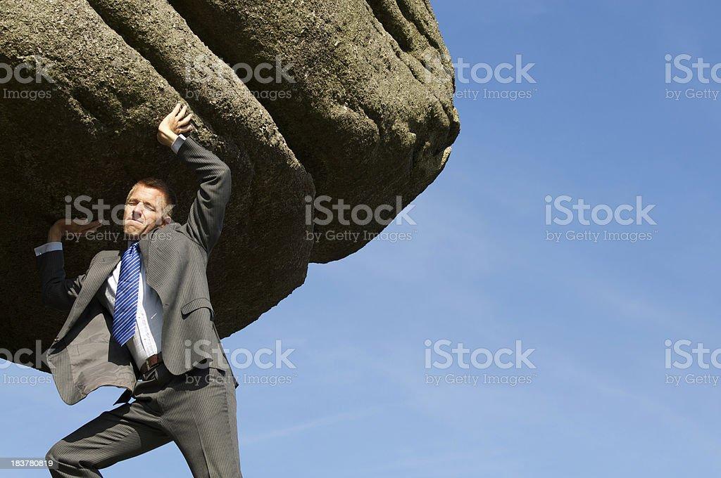 Businessman Struggles Heaving Massive Rock Boulder into the Sky stock photo