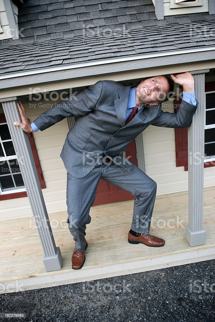 Businessman Struggles under Shrinking House royalty-free stock photo