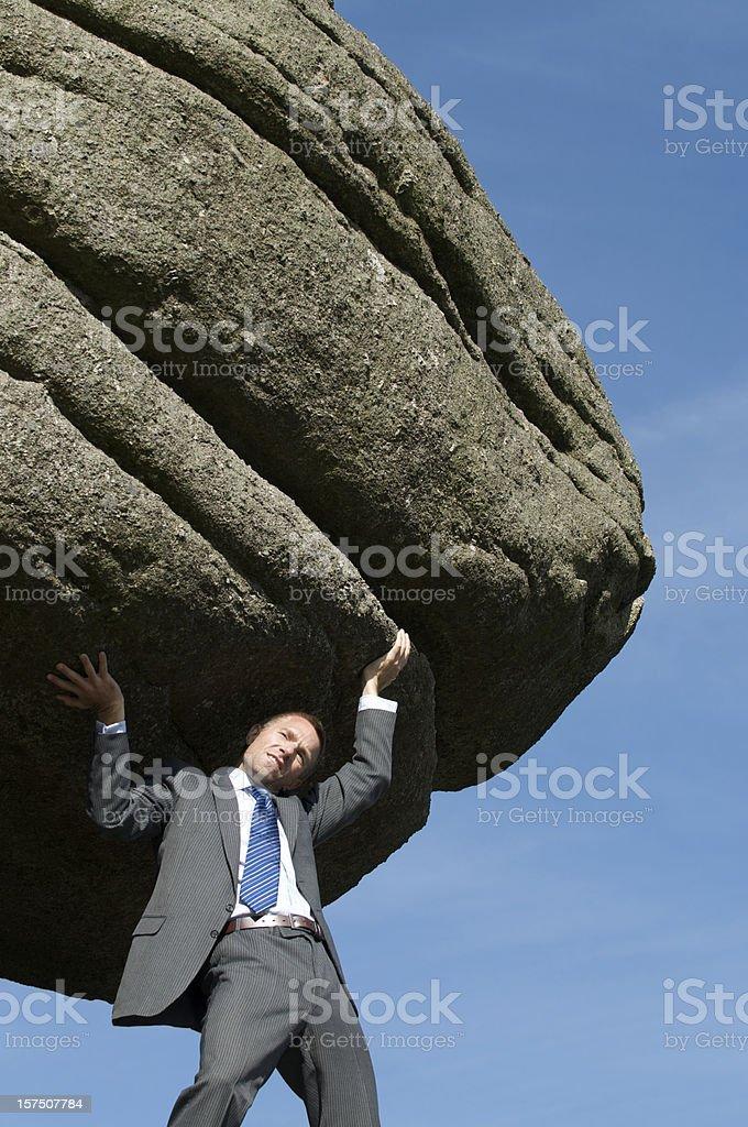 Businessman Struggling Outdoors Lifting Massive Heavy Boulder stock photo