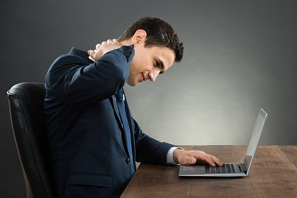 Businessman Suffering From Neck Pain Using Laptop At Desk Young businessman suffering from neck pain while using laptop at desk against gray background bad posture stock pictures, royalty-free photos & images
