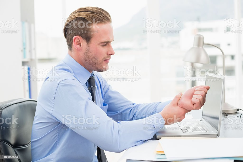 Businessman suffering from wrist pain stock photo