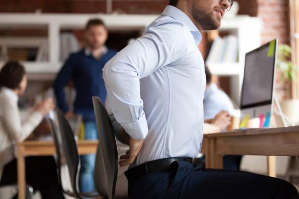 affärs man lider av länd ryggont sitter i delat kontor - kronisk sjukdom bildbanksfoton och bilder