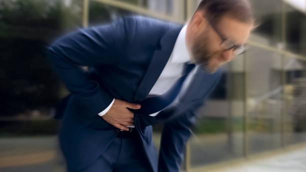 Businessman suffers from sharp stomach ache, gastritis, heartburn, dizzy effect stock photo