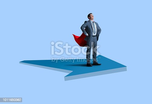 A businessman wearing a red cape stands proudly and attentively as he stands with his hands on his hips on a large arrow against a blue background
