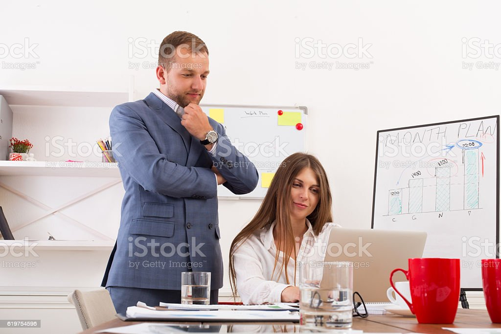 Businessman supervising his female assistant's work on laptop co stock photo