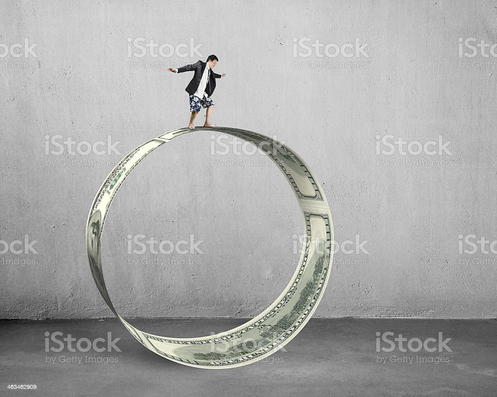 Businessman surfing and balancing on large money circle royalty-free stock photo