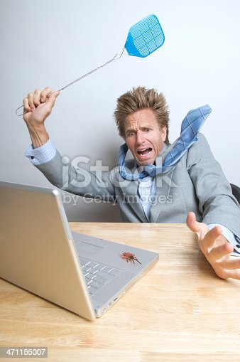 istock Businessman Swats Computer Bug on His Laptop 471155007