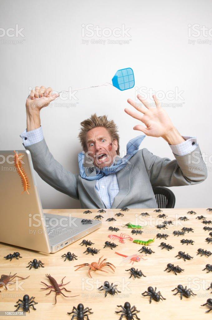 Businessman Swatting Computer Bugs on Desk royalty-free stock photo