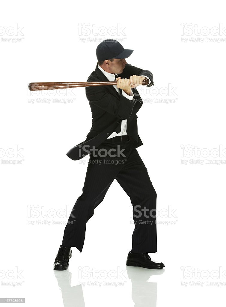Businessman swinging with baseball bat stock photo