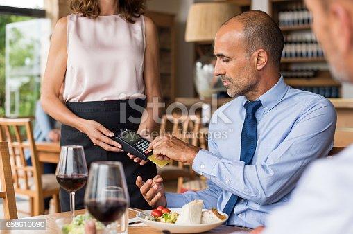 178974134 istock photo Businessman swiping credit card 658610090