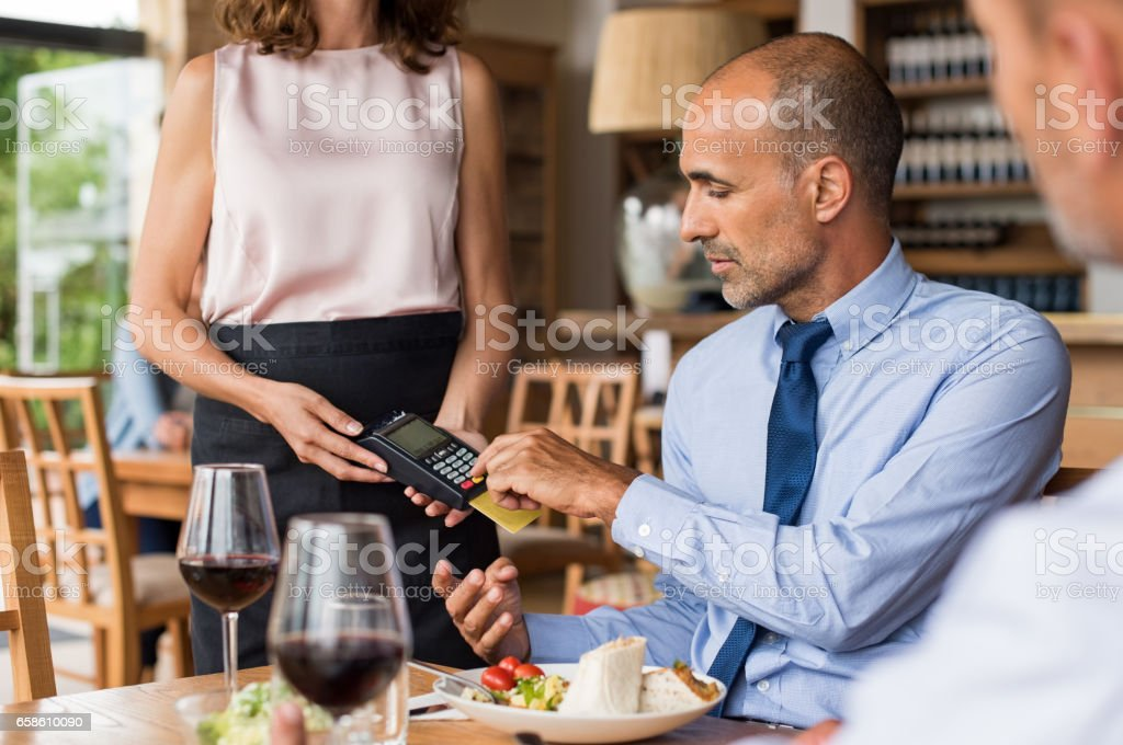Businessman swiping credit card stock photo