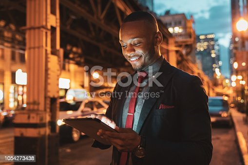 African american businessman looking into his digital tablet reading messages standing in the streets of downtown chicago at twilight - night, smiling happy. Downtown Chicago, Illinois, USA