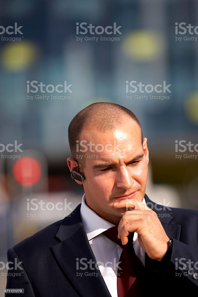 Businessman takes call on bluetooth earpiece. royalty-free stock photo