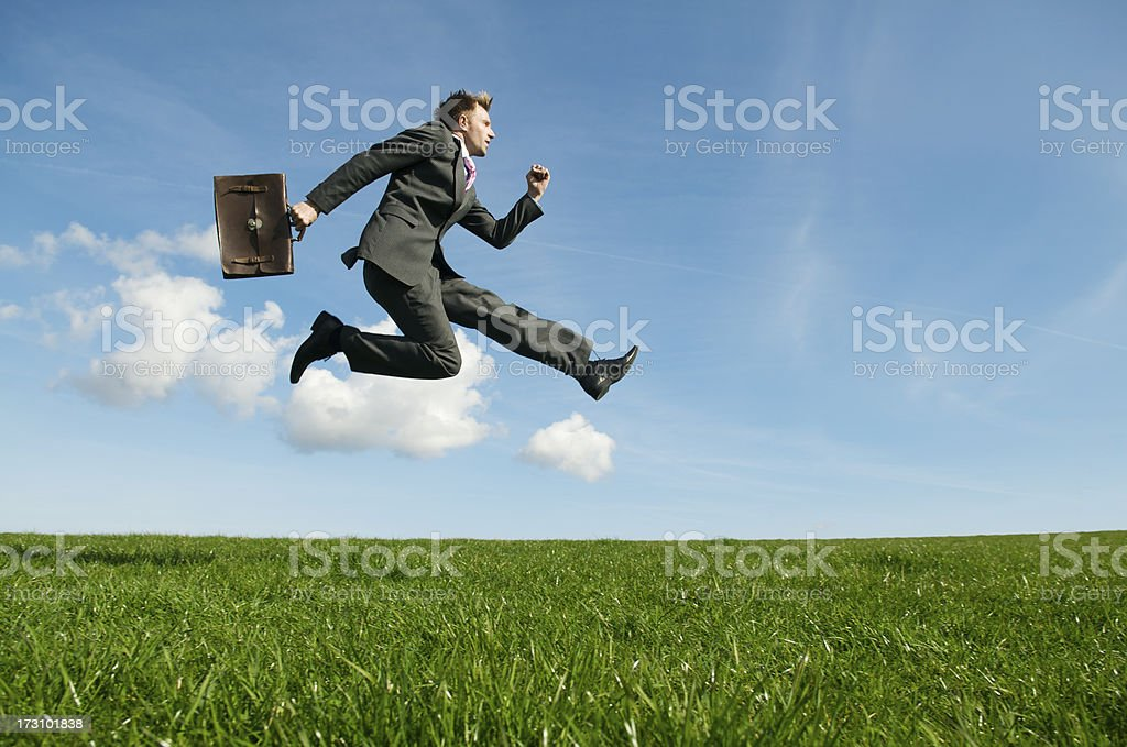 Businessman Takes Flying Leap in Meadow stock photo