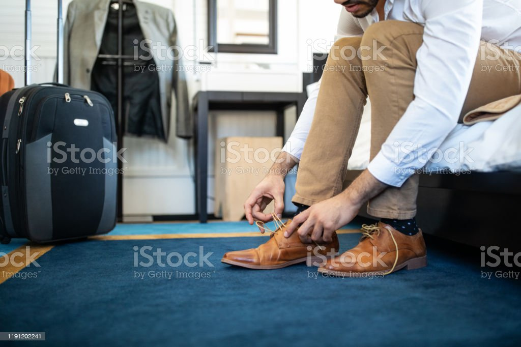 Businessman takes off his shoe in hotel room - Royalty-free Adult Stock Photo