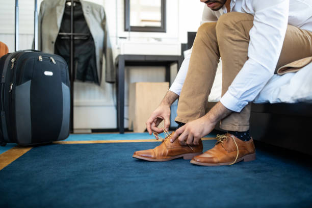 Businessman takes off his shoe in hotel room stock photo