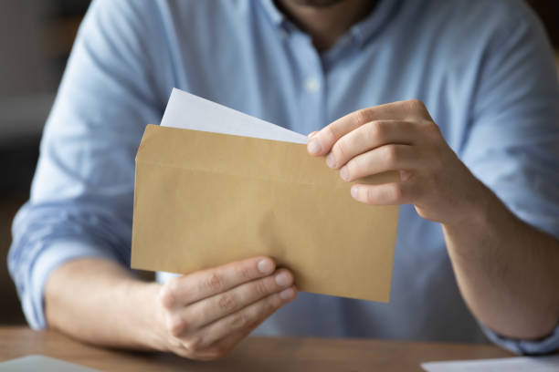 Businessman takes out letter from envelope with business news stock photo