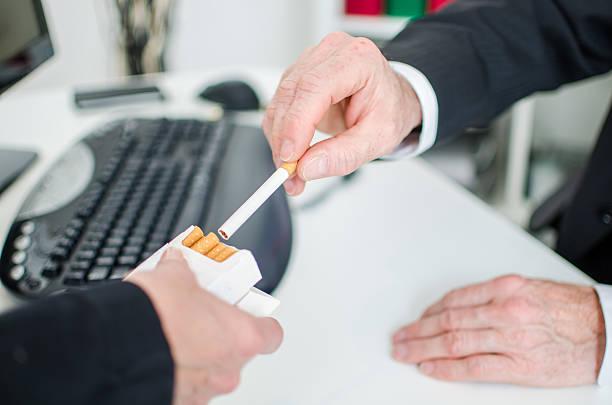 Businessman taking a cigarette stock photo