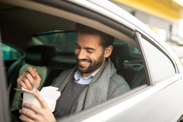 Businessman taking a meal in a cab stock photo