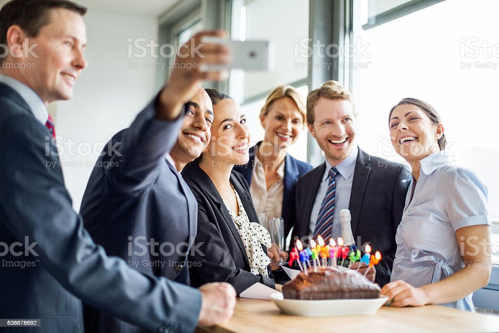 Businessman taking a selfie at birthday party in office - Photo