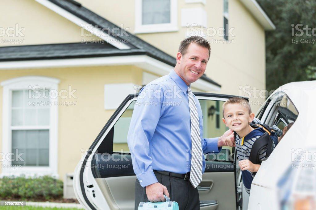 Businessman taking boy to school by car stock photo